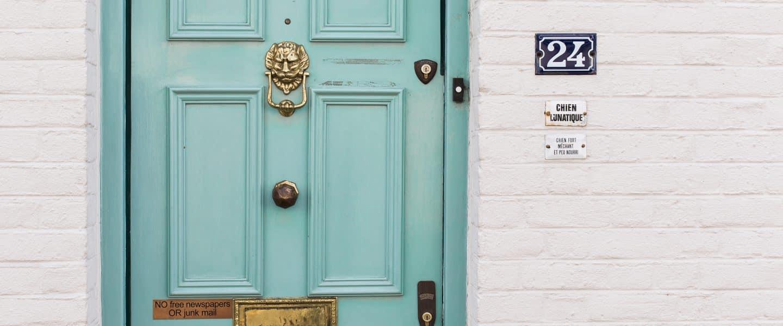 teal wooden door beside white concrete wall