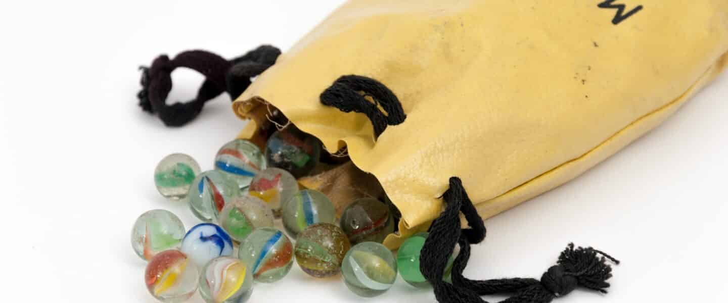 marble toy lot near yellow drawstring pouch