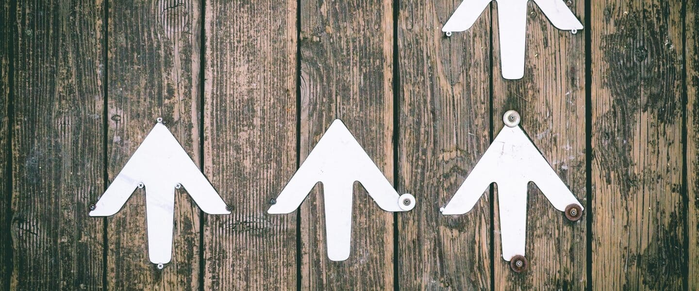 Several white arrows pointing upwards on a wooden wall