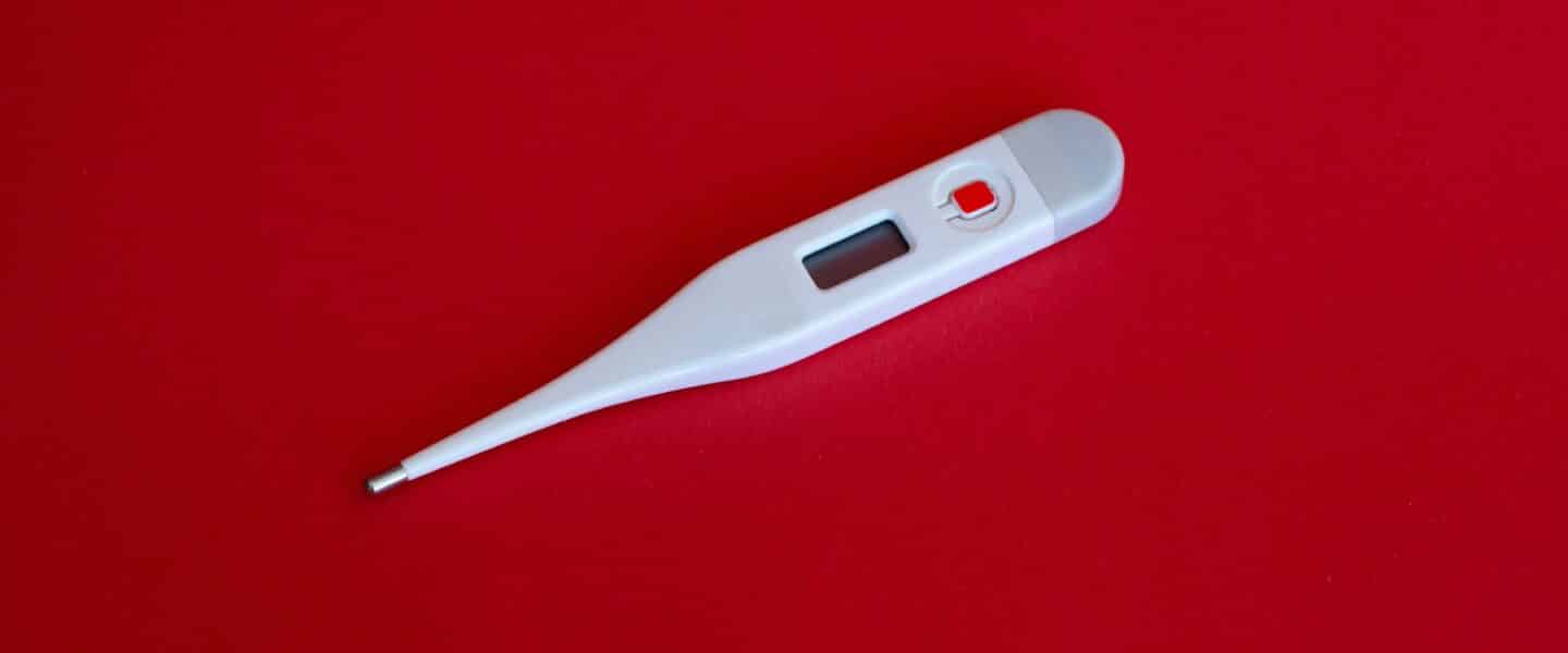 white thermometer on red surface