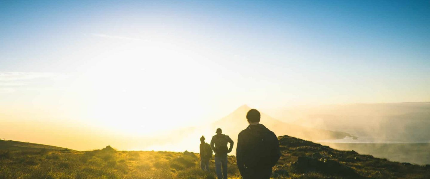 silhouette of three men falling in line while walking during golden hour