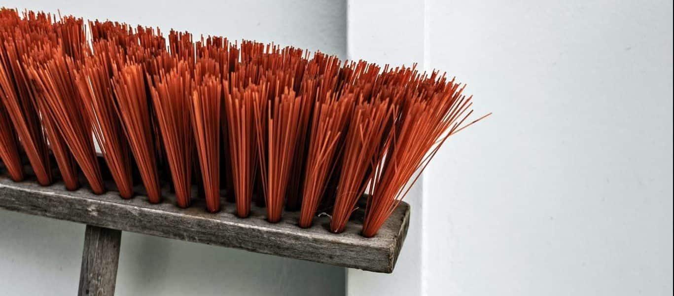 brown and orange push broom beside white wall