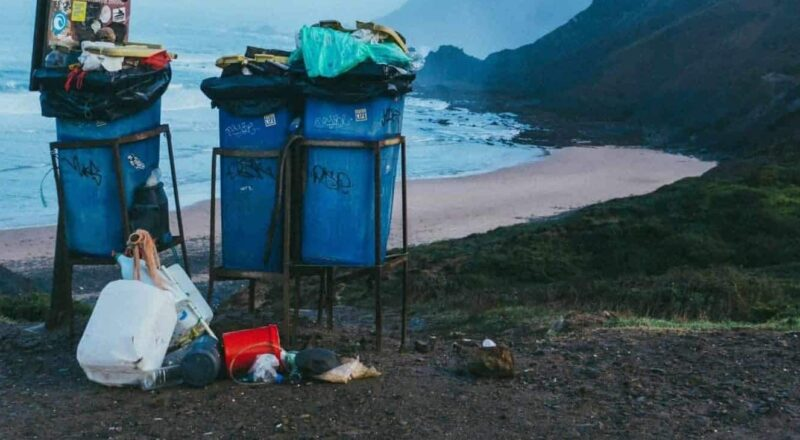 3 blue garbage cans in beach