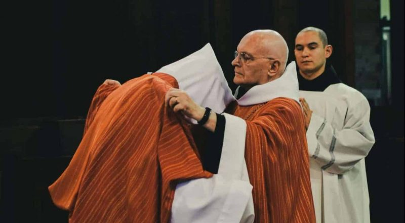 two priests in brown and white robes