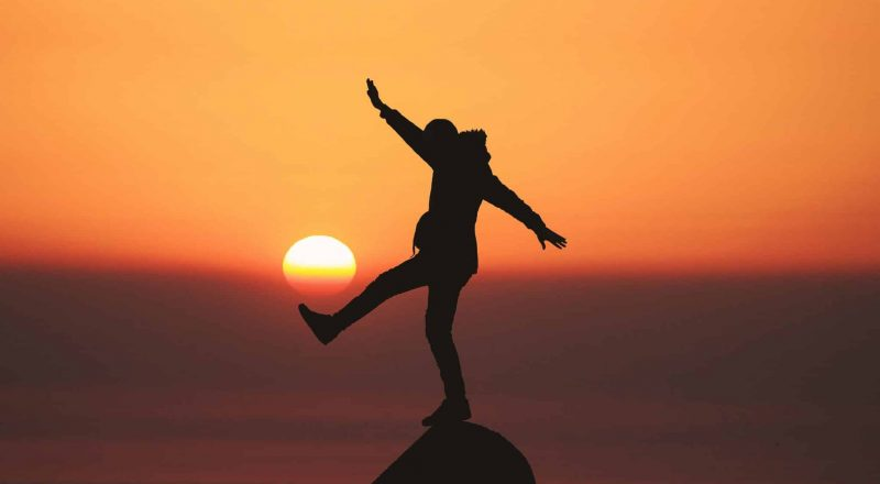 photo of silhouette photo of man standing on rock