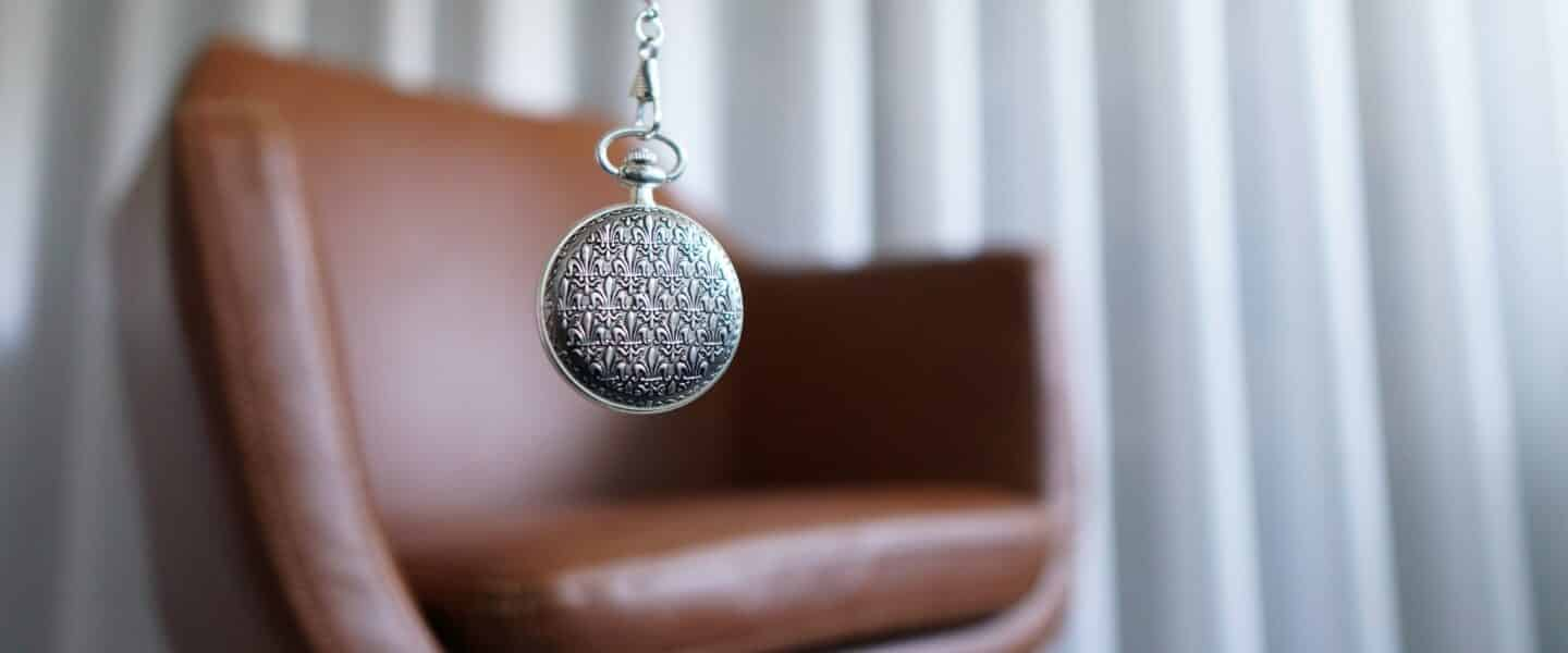 silver round pendant on brown wooden chair