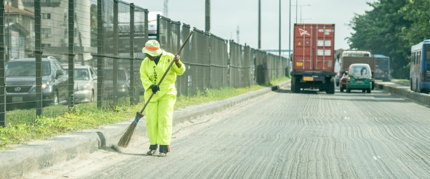 man in green jacket and green pants holding shovel walking on road during daytime