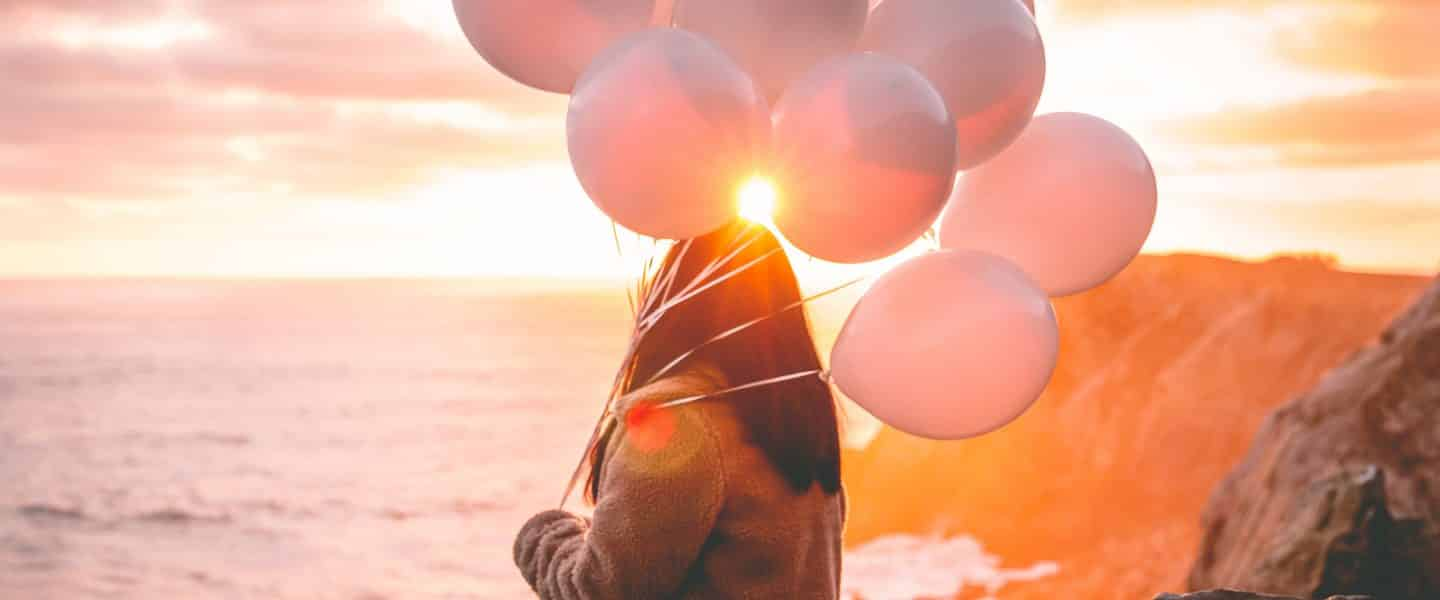 woman in brown jacket holding balloons on beach during sunset