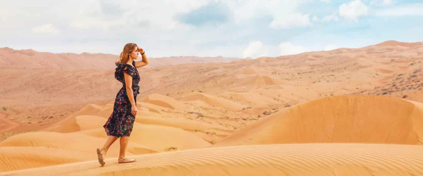 woman walking on sand dunes during daytime
