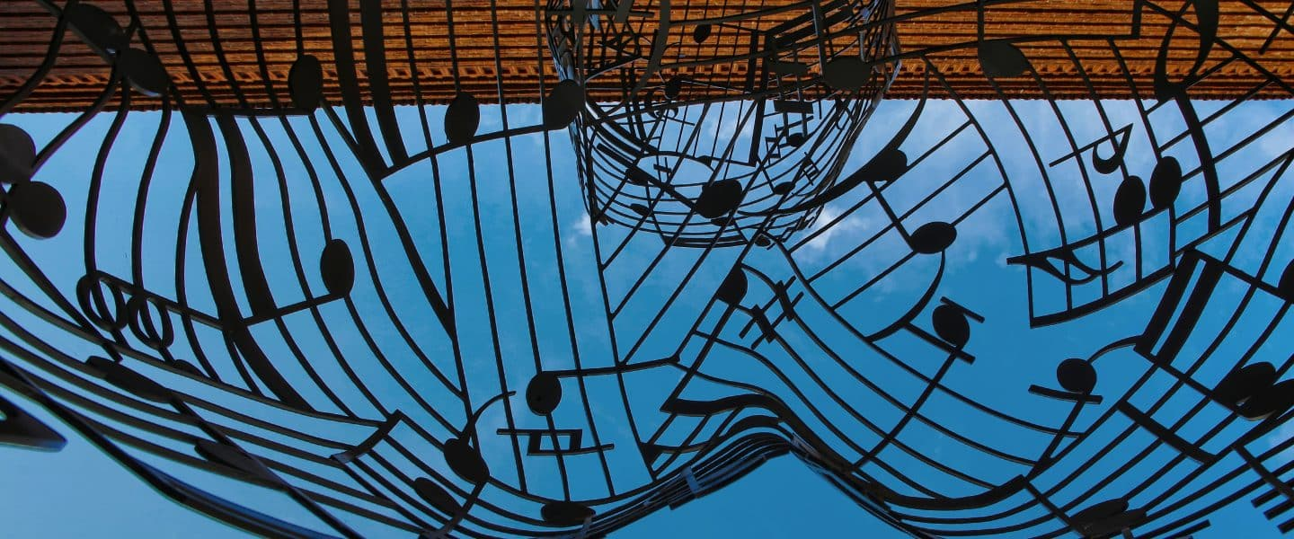 musical notes themed metal artwork under blue sky at daytime