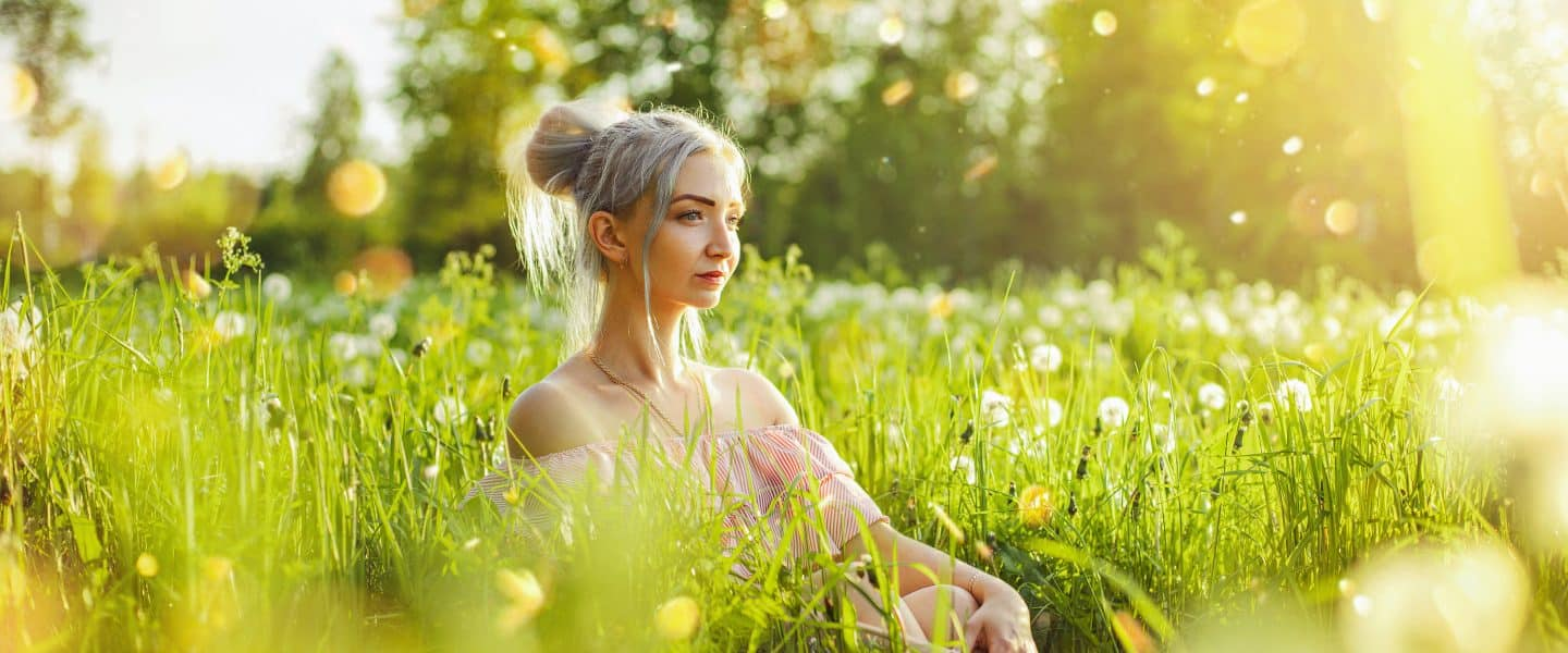 woman in white floral dress sitting on green grass field during daytime