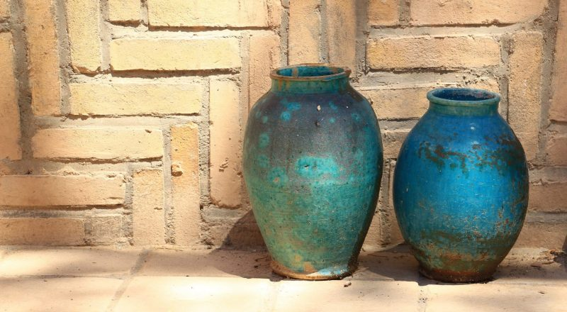 two blue ceramic vases near brown concrete wall