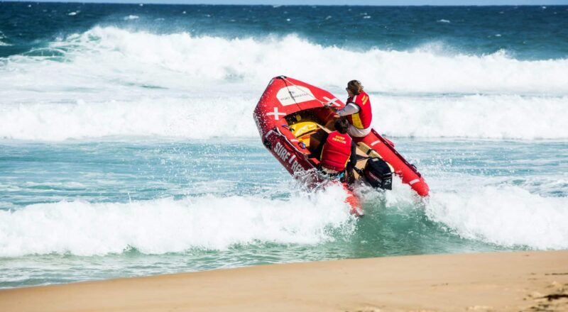 man in red and black suit riding orange and black inflatable boat on beach during daytime