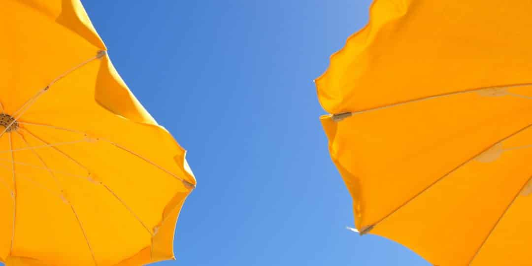 two yellow patio umbrellas under blue sky during daytime