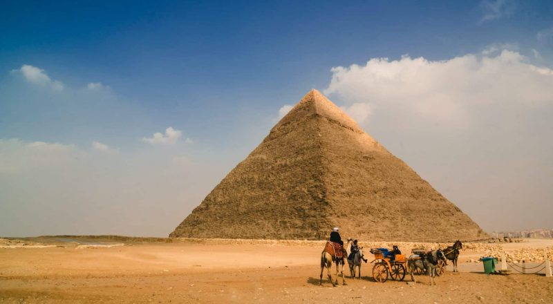 people riding horses on brown sand near pyramid during daytime