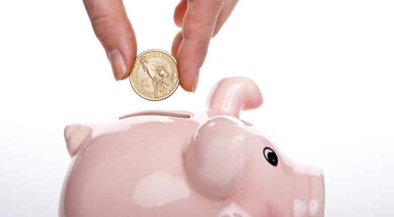 silver round coin on white ceramic pig coin bank